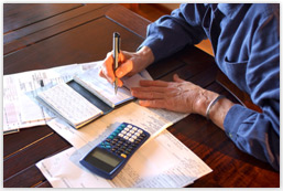 An older adult writes a check on a desk.